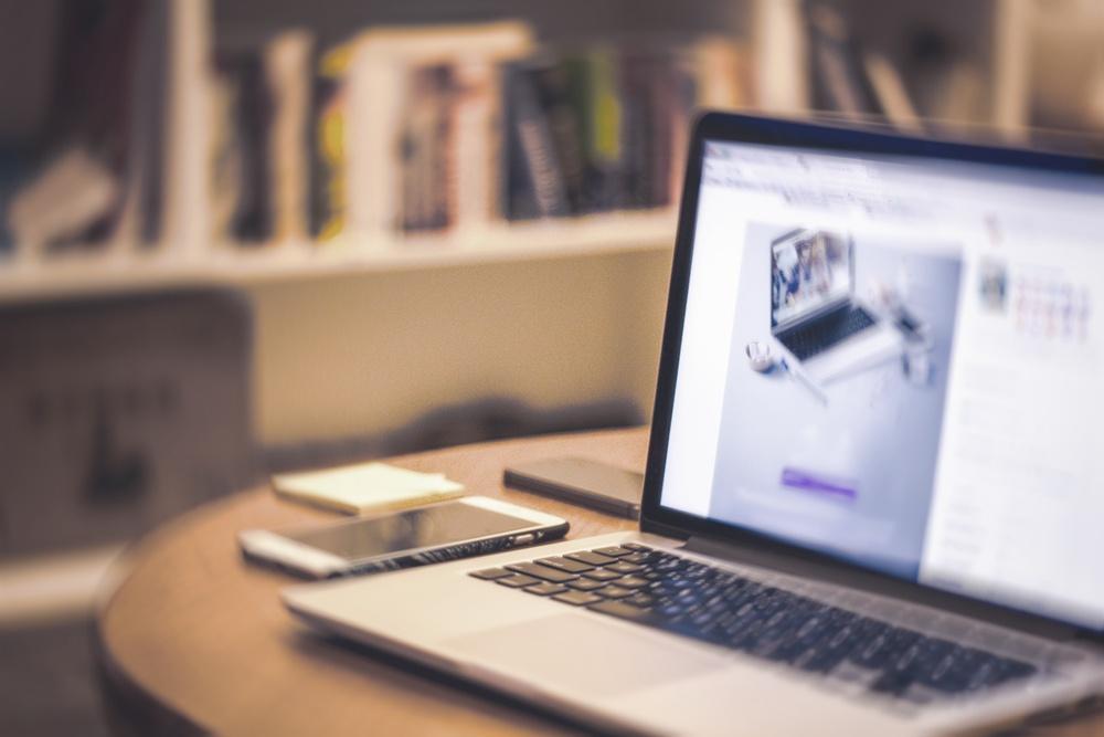 Macbook sobre mesa con libreria al fondo
